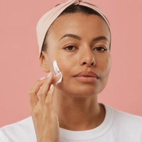 person cleaning face with toner on cotton pad