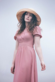 beautiful woman with long curly hair in a pink dress with a sunhat