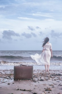 a woman is walking into the sea, leaving her luggage behind her