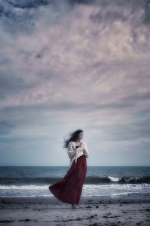 a woman in a red dress and a white shawl is standing on the beach