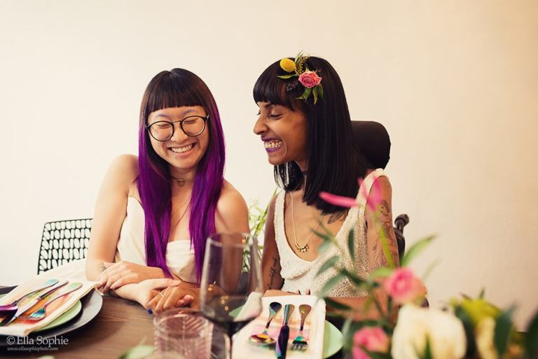 Disability Rights Wedding Editorial, Brides sitting at table holding hands by Ella Sophie Oakland