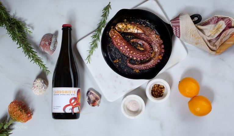 Styled wine bottle product photography by San Francisco photographer Ella Sophie. Carboniste Wine bottle flat-lay with cooked octopus, citrus, and sides. Fun modern & creative product photography for women owned brands.