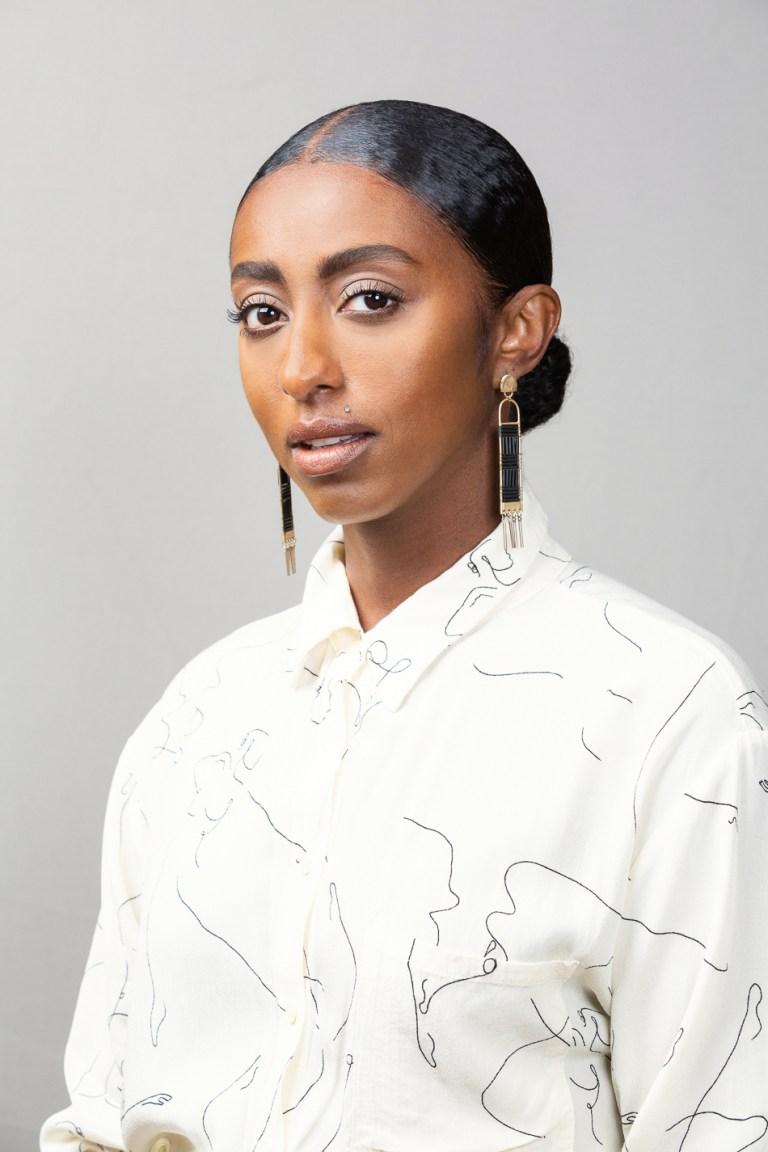 Professional Portrait for speaker Kalkidan Gebreyohannes by Oakland portrait photographers Ella Sophie. Black woman entrepreneur wearing white blouse with gray background.