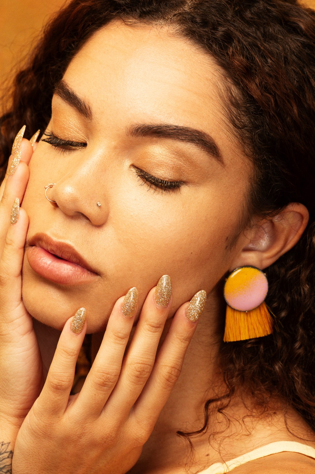 Jewelry photography by Oakland photographers Ella Sophie, Model with gold nails and modern earrings