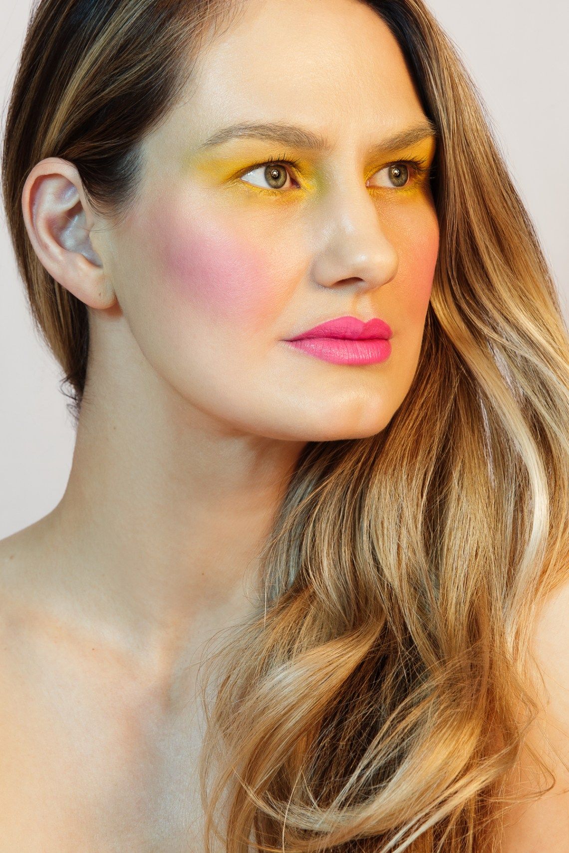 Beauty photography portraits of blonde model with blush, pink lips and yellow eye makeup