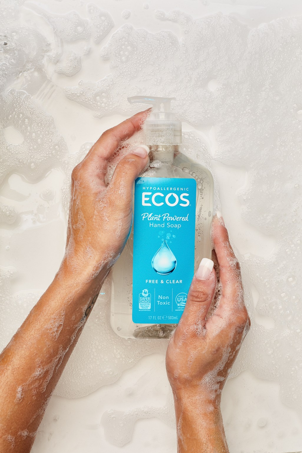Still life product photo of hand soap in soapy water with manicured hand. Photographer Ella Sophie