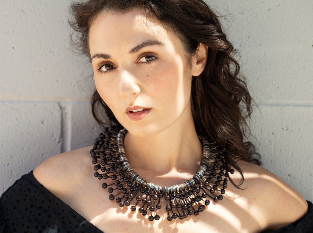 Jewelry lifestyle advertising image by women photographers Ella Sophie. Model Zoe West wearing intricate metal necklace.