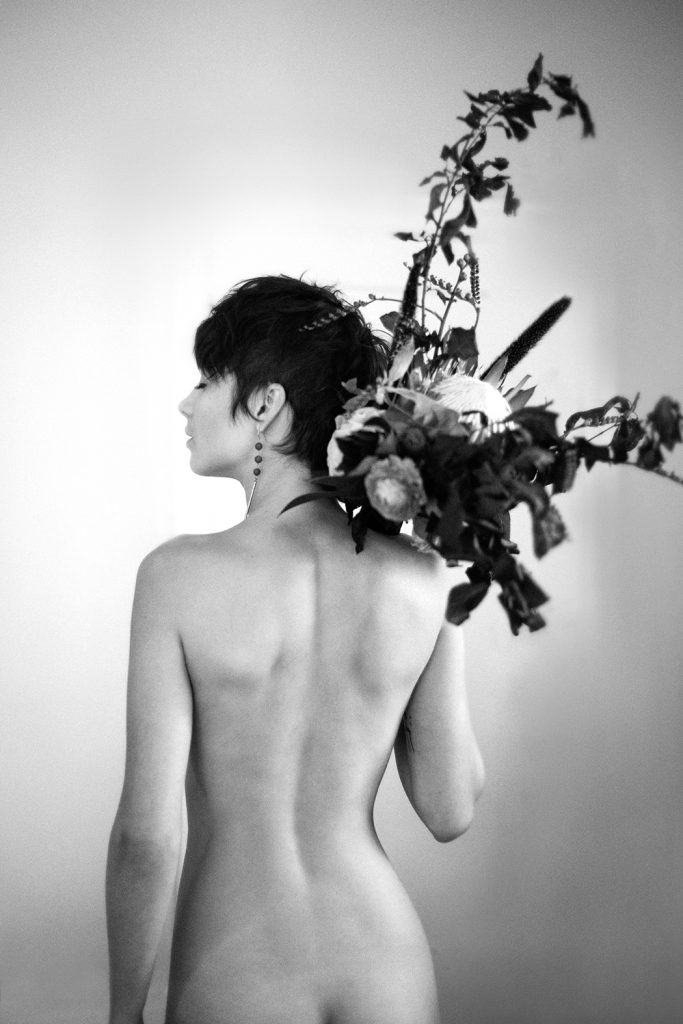 Nude feminist boudoir session of woman holding flowers. Black and white image by Ella Sophie photographer in Bay Area.