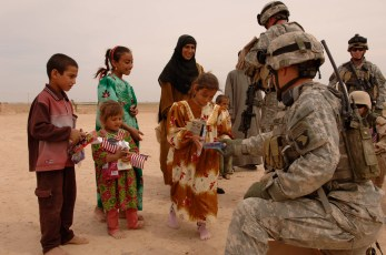060401-A-5747J-078 Soldiers from the U.S. Army's 4th Battalion, 101st Aviation Regiment hand out small American flags and gifts to children during a goodwill visit to a village outside of Tikrit, Iraq, on April 1, 2006. The items were donated by U.S. citizens to distribute to Iraqi citizens. DoD photo by Staff Sgt. Alfred Johnson, U.S. Army. (Released)