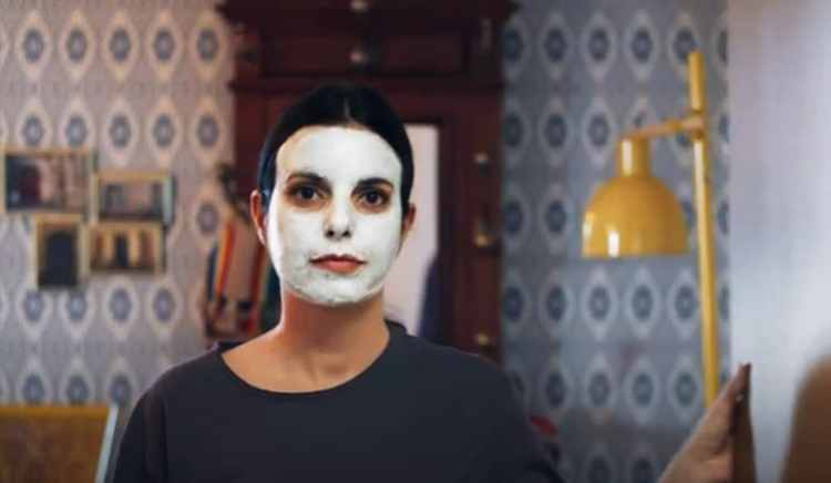 mujer joven con mascarilla en la cara abre la puerta en la nueva campaña de Just Eat