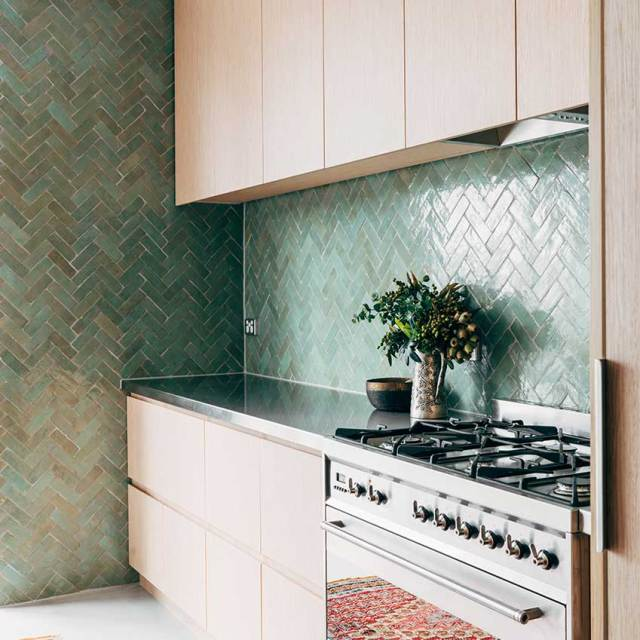 Fresh aquamarine herringbone tiles, rom Tiles of Ezra, used on the wall and splashback of this kitchen bring a natural vibe to this eco-minded home in a leafy Melbourne suburb. For more details see ELLE Decoration Kitchens Volume 2. Link at end of post.