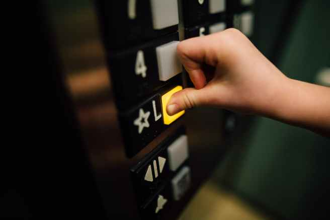 anonymous person pressing button of lift