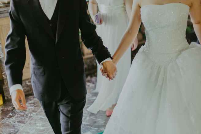 woman wearing white wedding gown holding hands with man while walking