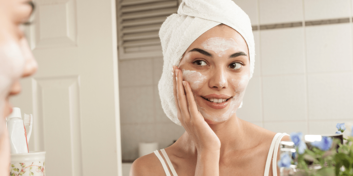 woman looking into mirror with towel on head putting on skincare atlanta medical spa