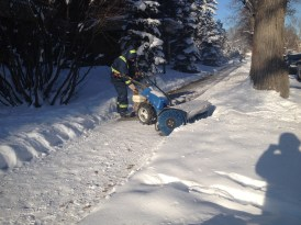 A sweeper clears the sidewalks. Home owners and businesses must clear the sidewalks within 48 hours of snowfall. There's a lot of equipment for this!