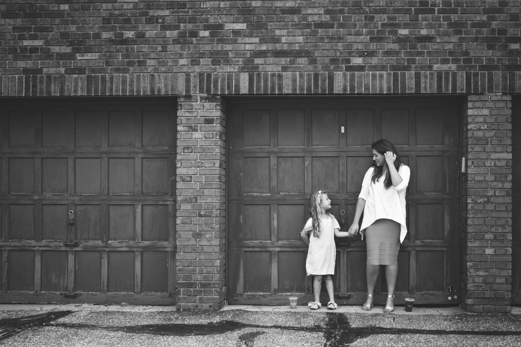 black and white photo of little girl and her mom posing in front of garage doors