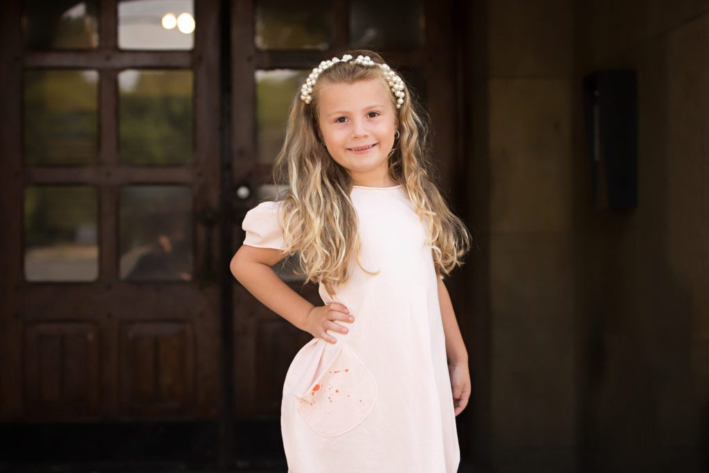 Little girl posing in front of old building entryway