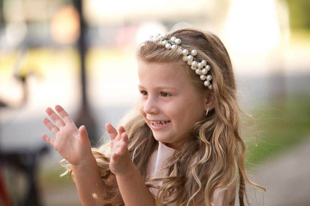 little girl reaching her hands out and smiling