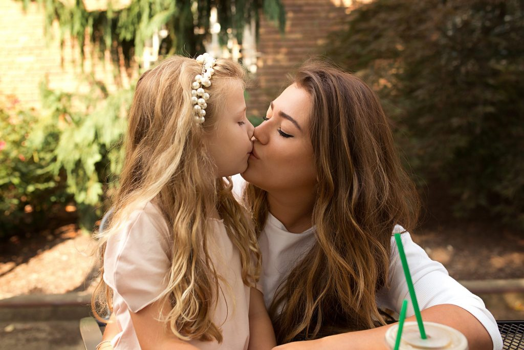 little girl and her mom kiss while on a coffee date