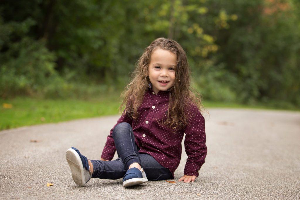 three year old boy crosses his legs sitting on a path