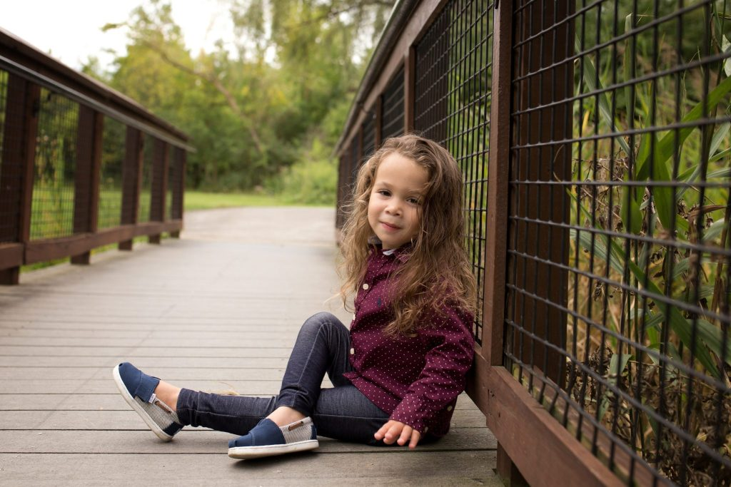 little boy poses on a bridge with his right leg crossed over his left