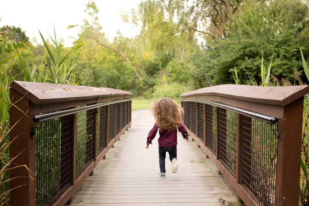 back of little boy with long brown hair running down a bridge