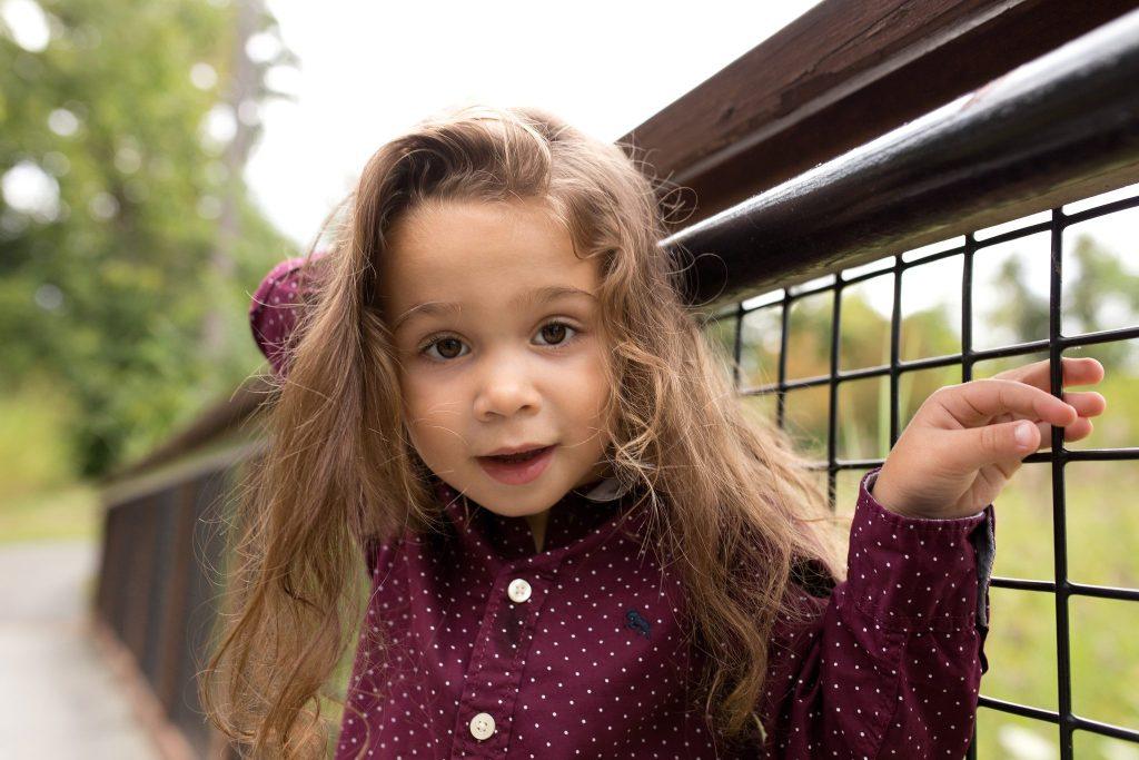 little boy with long hair poses on a bridge