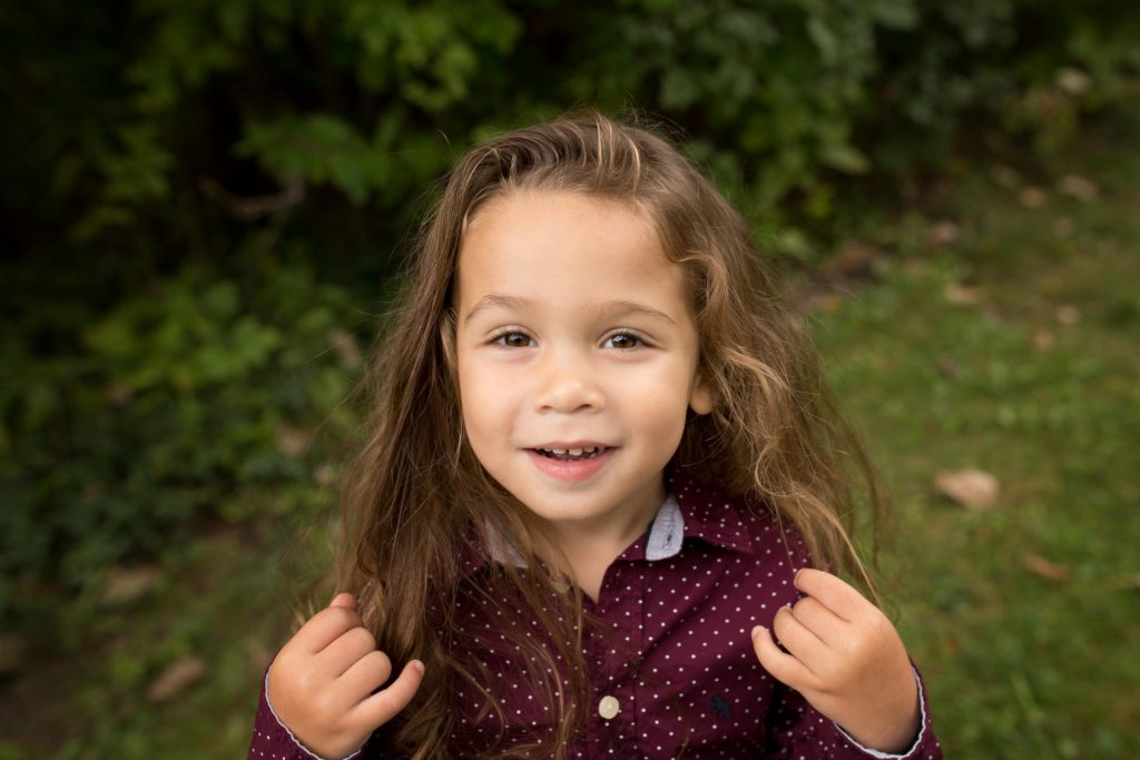 portrait of a three year old boy with long brown hair