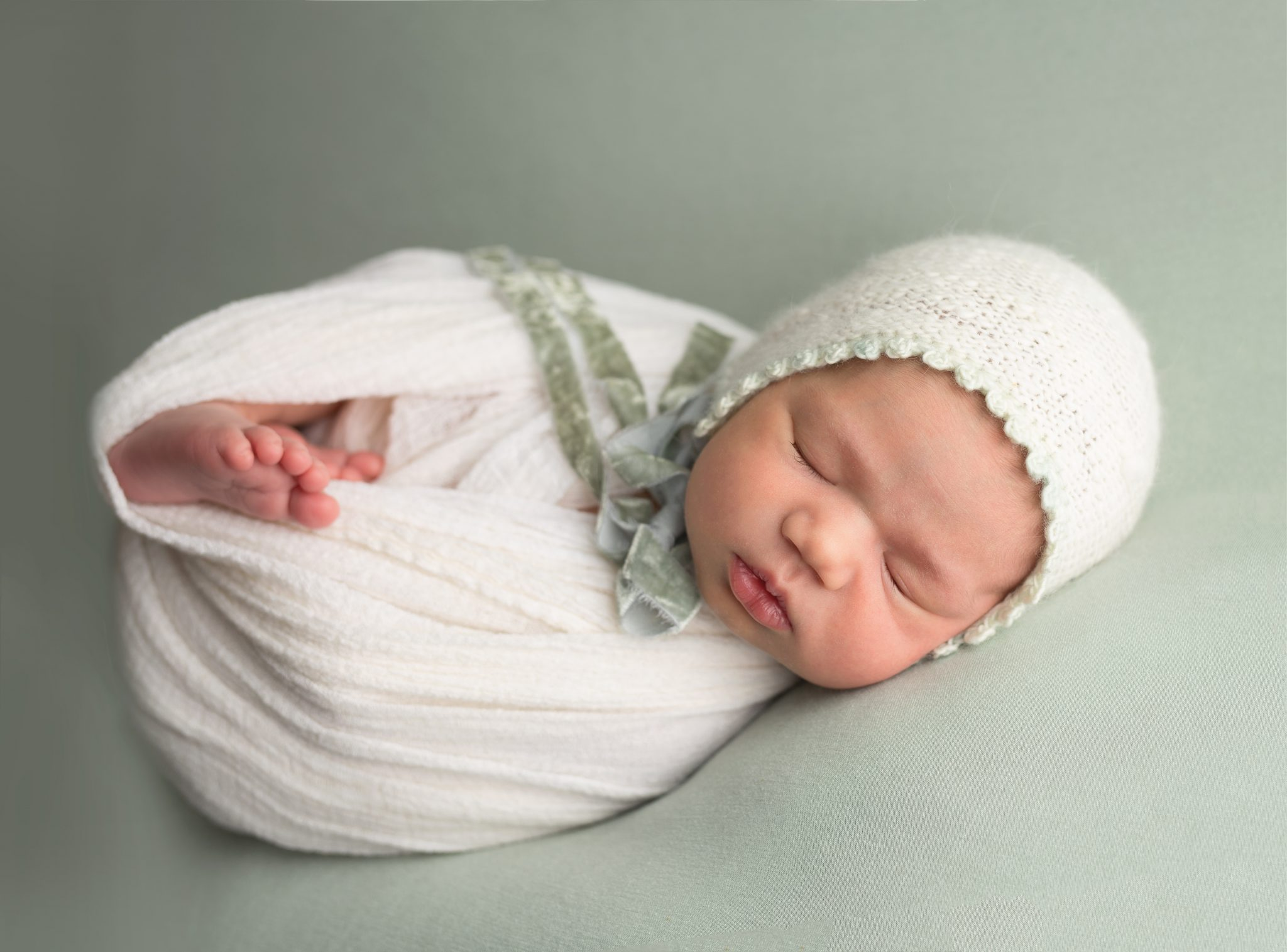newborn baby girl on sage colored background in white bonnet and white wrap