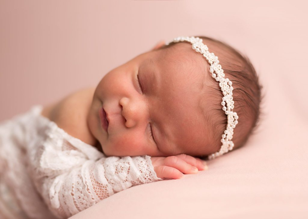 baby girl in pearl headband on pink background