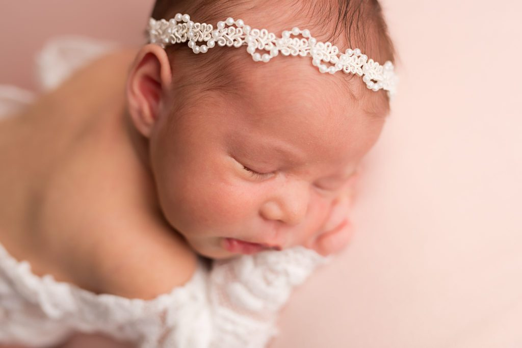 newborn baby girl in pearl headband on pink background