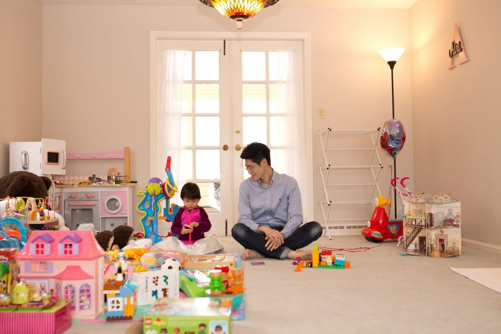 two year old girl plays with her father in her playroom