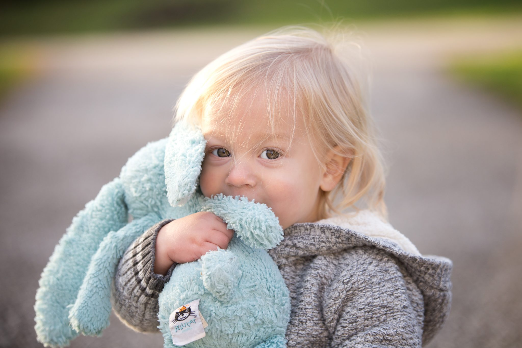 baby boy snuggles his blue plush bunny in a park in Beachwood