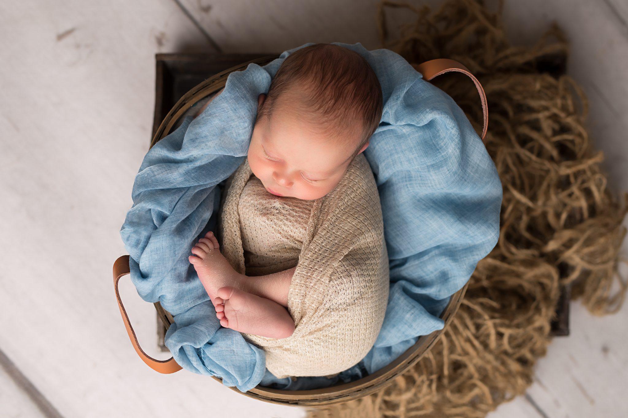 newborn baby boy in a biege wrap