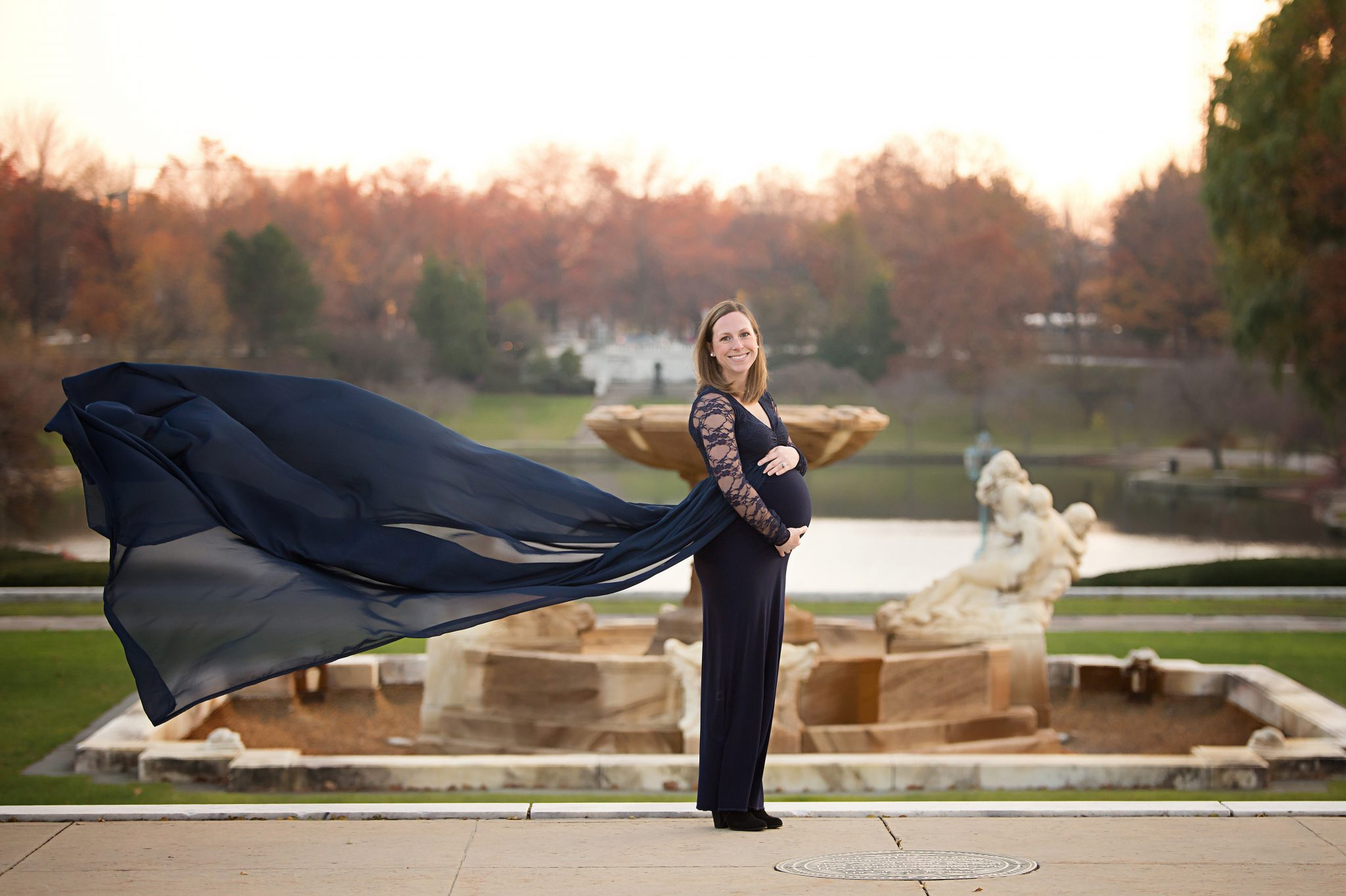 pregnant woman in navy gown in front of a fountain