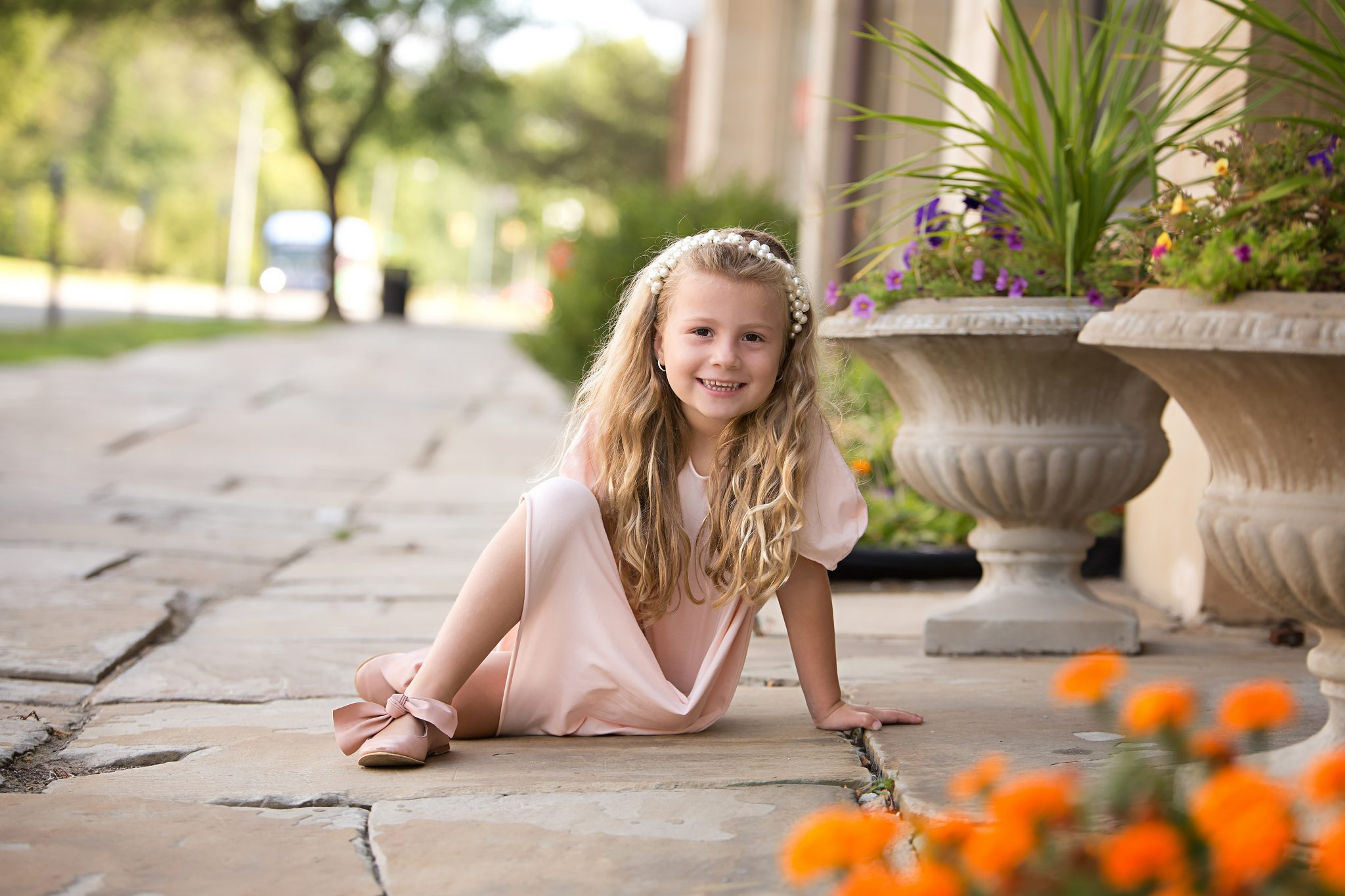 five year old blonde girl in peach colored dress sits on stone sidewalk with flowers around