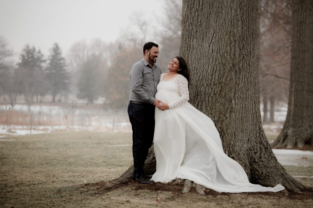 Beautiful couple laughing during their maternity session at acacia reservation