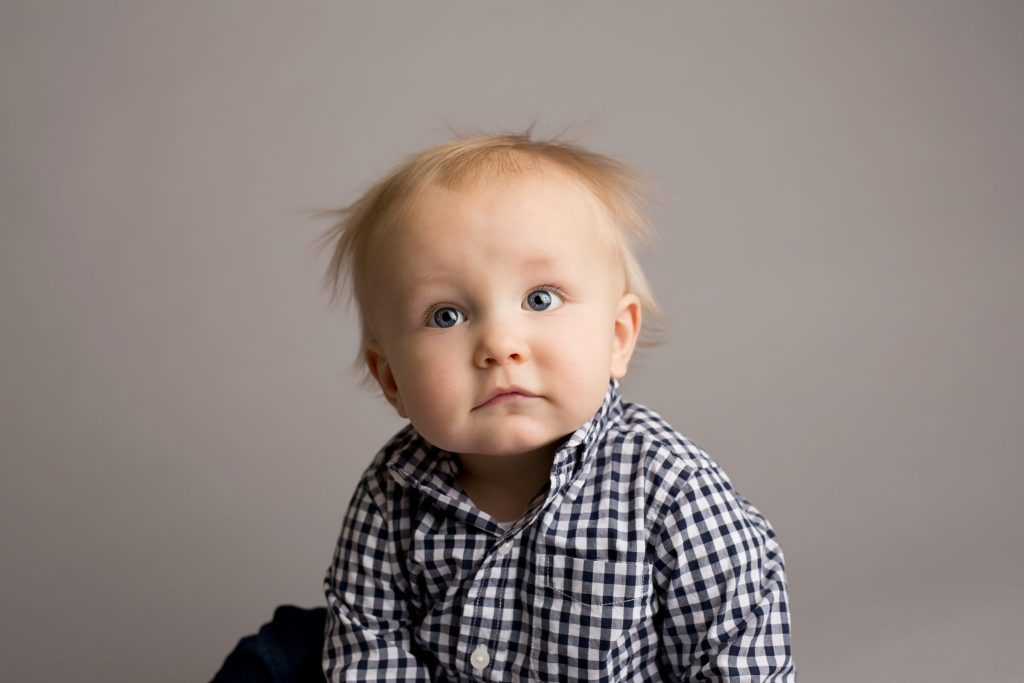 one year old baby boy in studio against grey backdrop