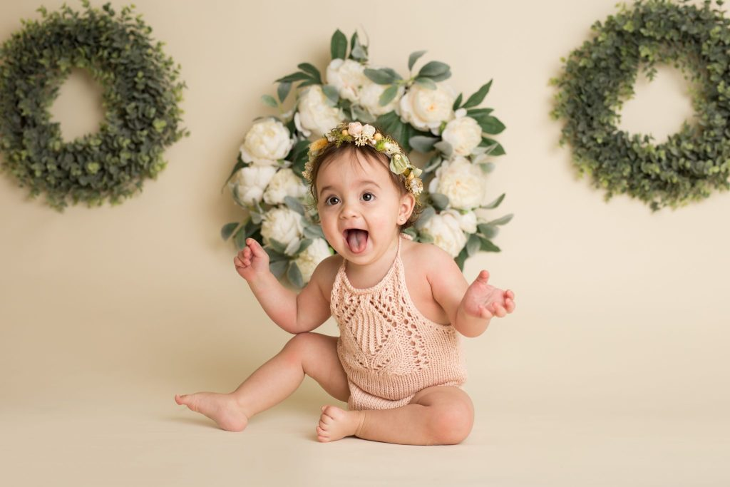 one year old girl at her in-studio session wearing a peach romper and a floral wreath