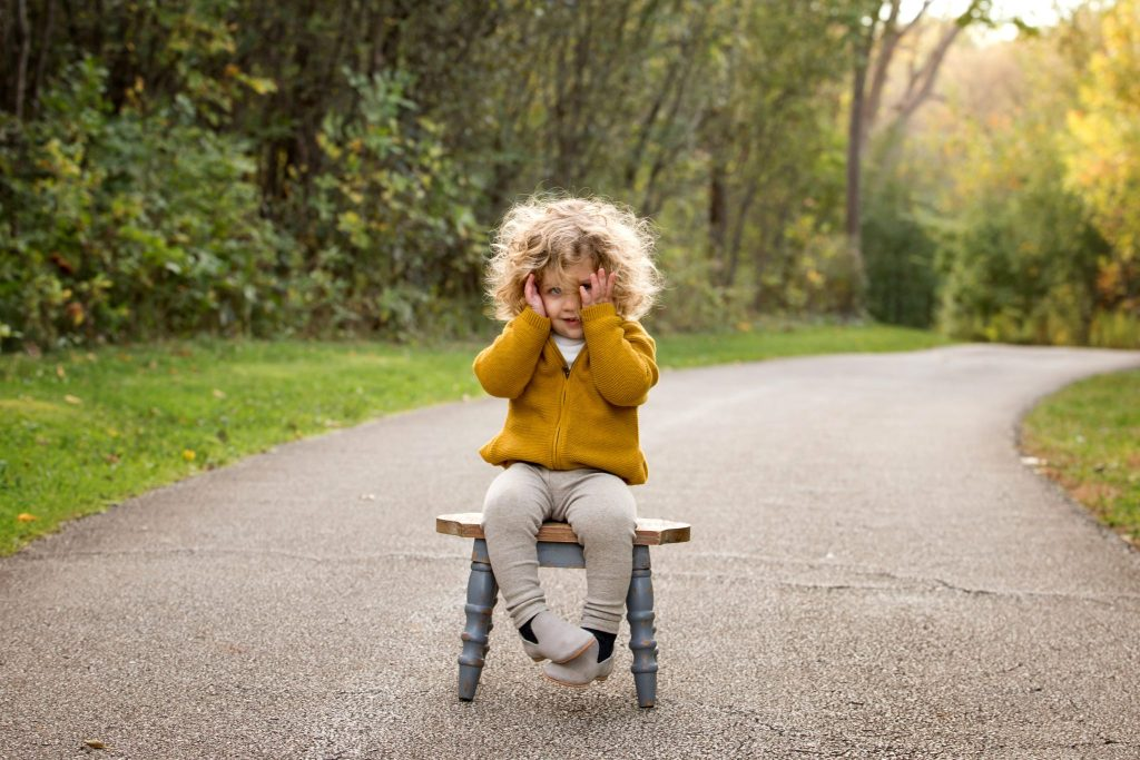 adorable two year old boy with big blonde curls sit on a stool outdoors