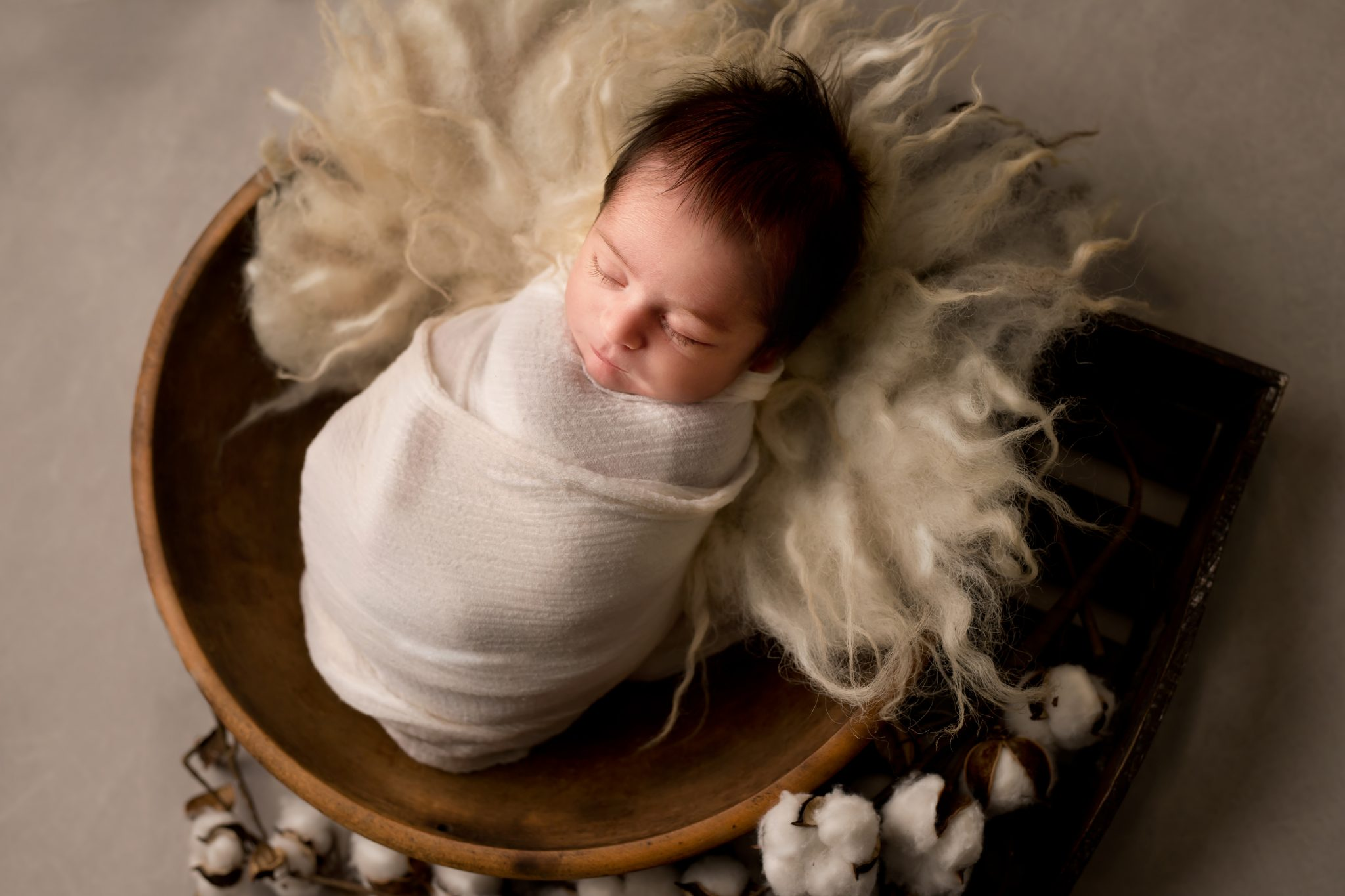 newborn baby boy in off white wrap in a wooden bowl
