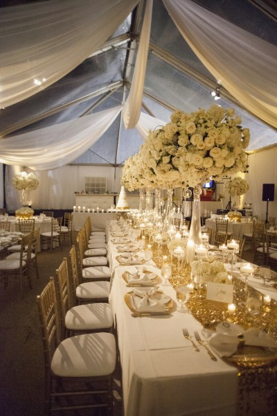 gold and white centerpieces , clear top tent