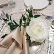 place setting, napkins, greenery, rose