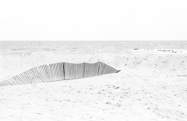 a black and white image of a fence on a beach