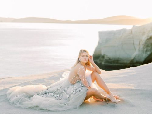 Bride sitting on the rocks in Milos Sarakiniko beach
