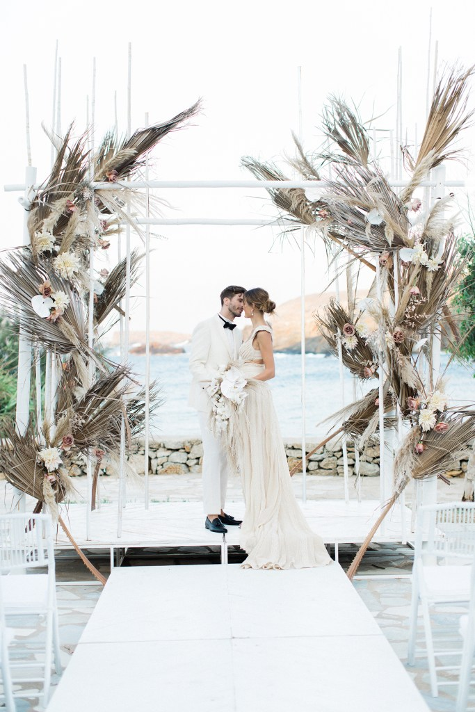 Bride and Groom Getting married under the Stylish Bohemian Chuppah Love Story in Mykonos