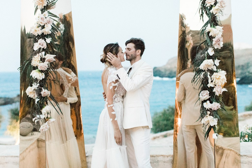 Bride and Groom Kissing in front of the Mirror Columns backdrop in Mykonos