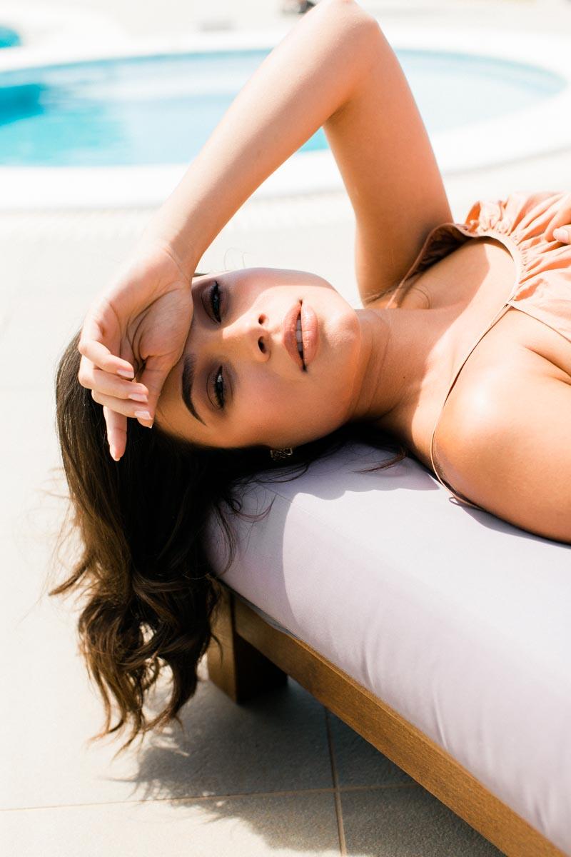 Girl lying on a sunbed by the pool in Greek summer in Kalita dress