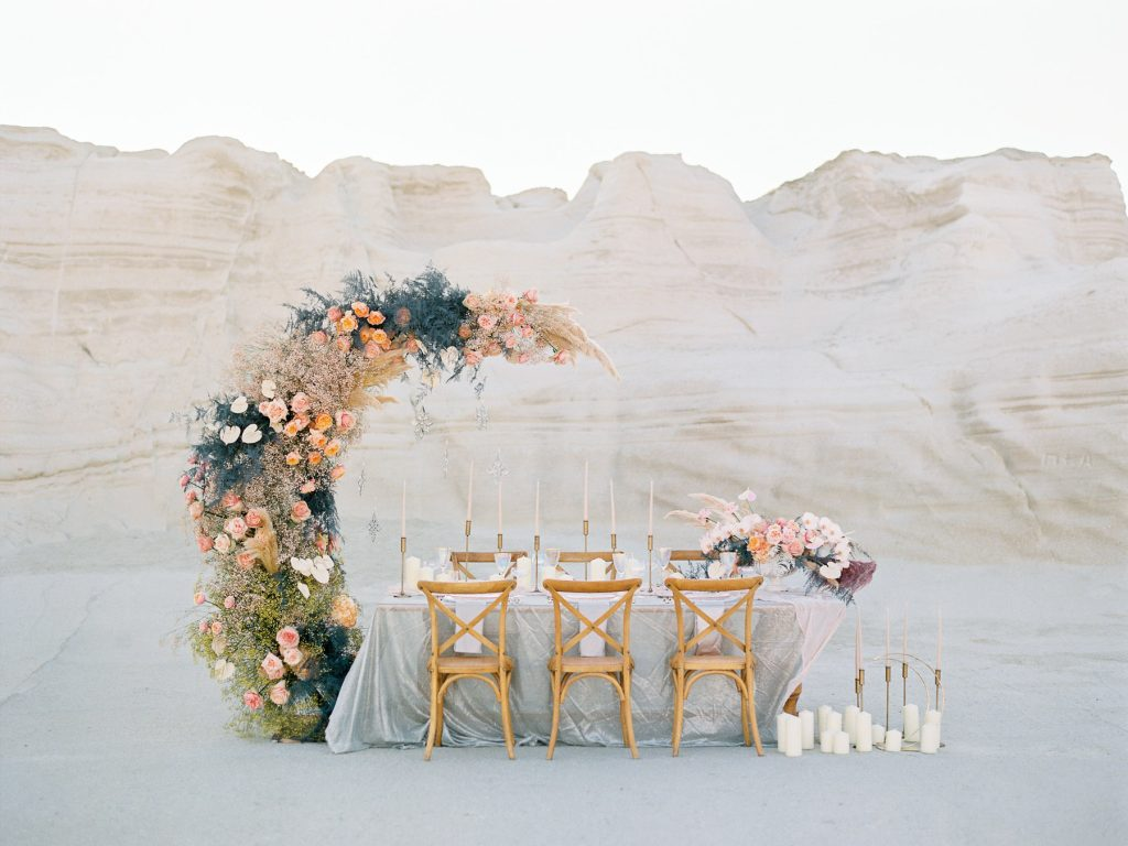 lush table setup with big lunar floral arrangement in Milos