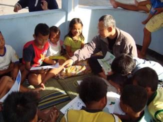 Gunawan explaining the drawings to kids in Sumber